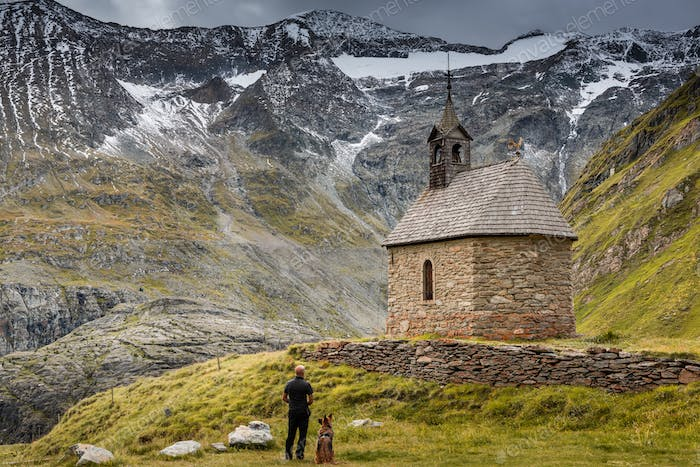 Adventure Man with Dog at Lonely Chapel in High Austria Alps Mou