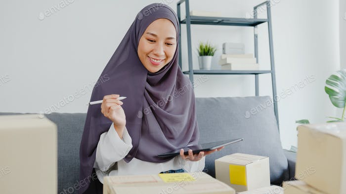 Young Asia muslim businesswoman check product purchase order on stock and save to tablet computer