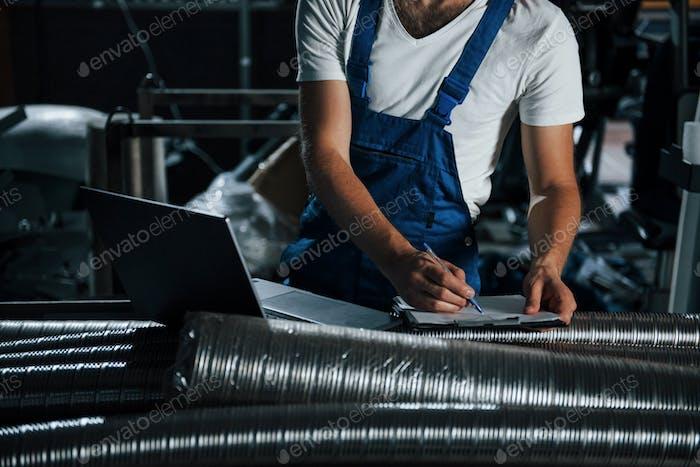 Результаты проверки. Человек в форме работает над производством. Современные промышленные технологии