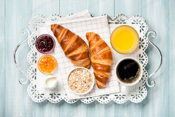 Breakfast with croissants, coffee, jam, orange juice and muesli