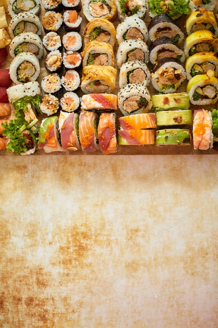Wooden board with assortment of various kinds of sushi rolls. Japanese food concept