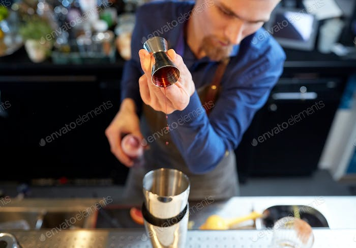 bartender with shaker preparing cocktail at bar