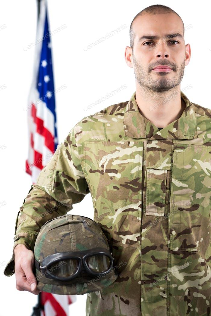 Portrait of smiling soldier standing with combat helmet