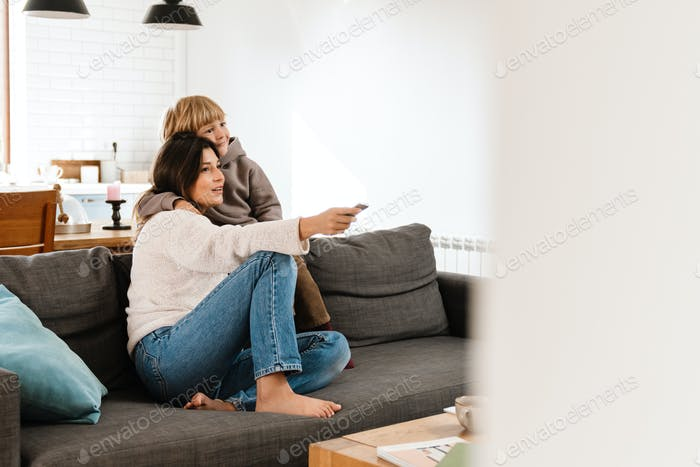 Woman watching tv at home with her son