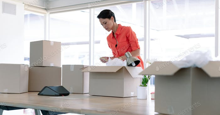Caucasian businesswoman unpacking office belongings from cardboard boxes on table in new office