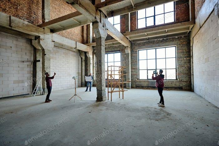 Zwei junge Auftragnehmer fotografieren unfertige Struktur innerhalb des Gebäudes