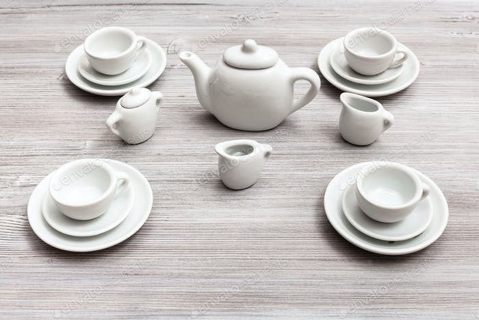cups with saucers and tea set on gray brown table
