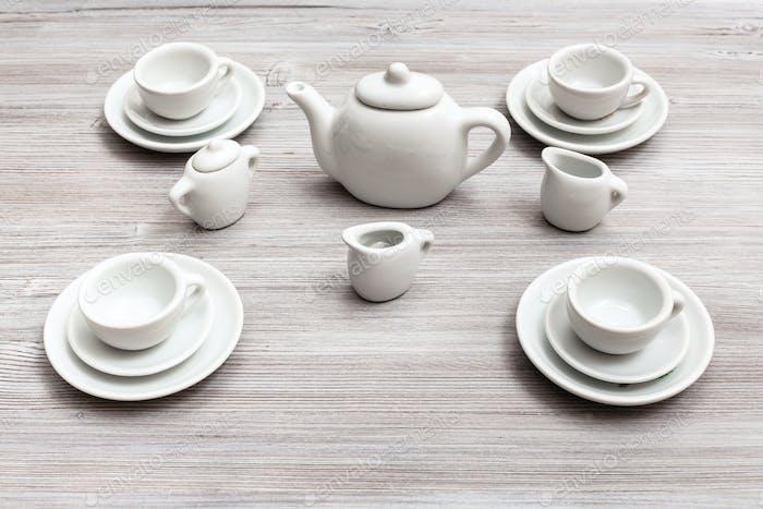 Tassen mit Untertassen und Tee-Set auf graubraunem Tisch