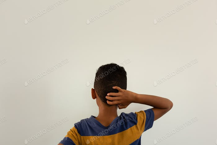 Rear view of mixed-race boy with hand behind head standing against white background