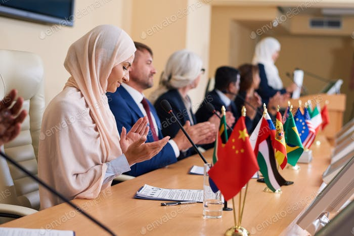 Group of contemporary intercultural delegates clapping hands
