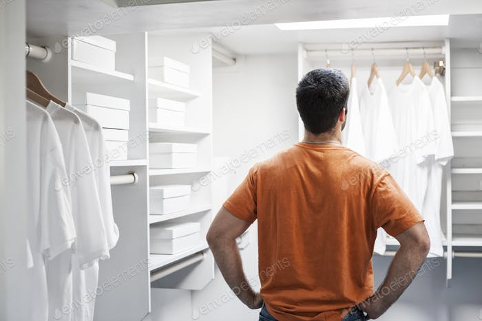 Hispanic man in a closet full of white clothes.