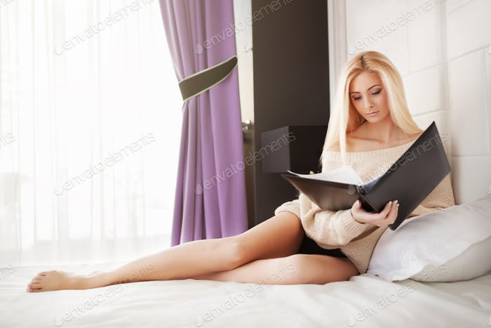 Yong woman reading documents in bedroom