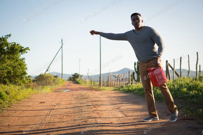 Man with petrol can hitchhiking at countryside