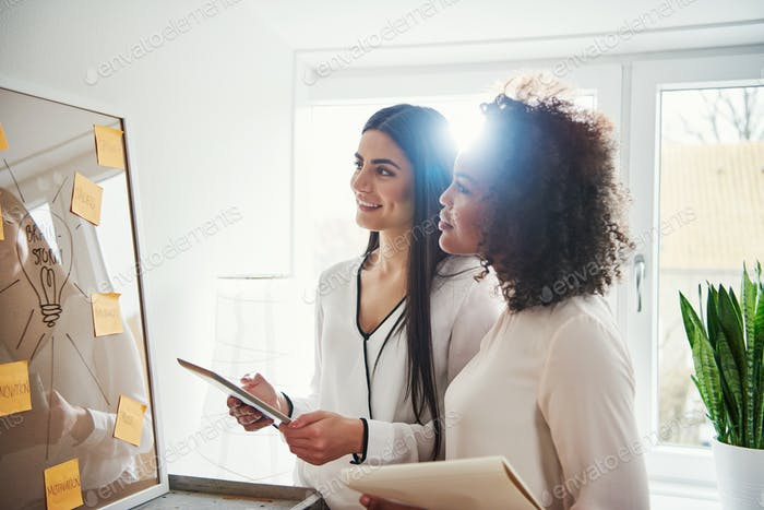 Two pretty cheerful multiracial designers with tablet