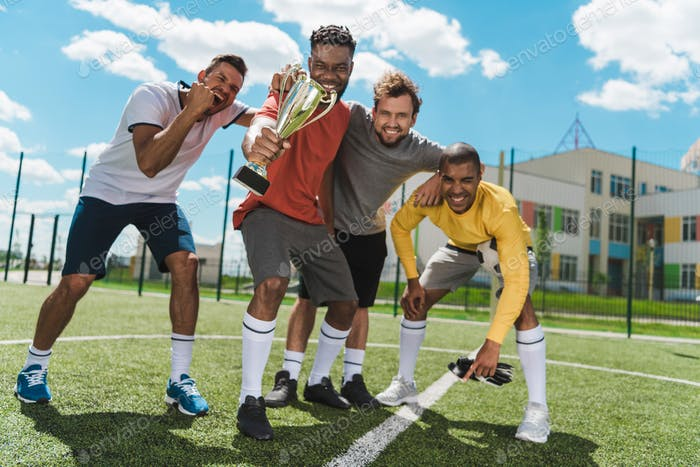 happy multiethnic soccer team with goblet standing on soccer pitch