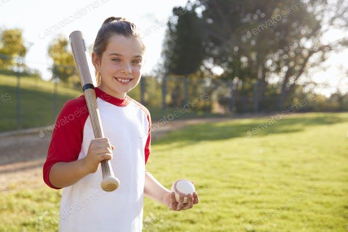 Chica joven sosteniendo béisbol y bate de béisbol mira a cámara