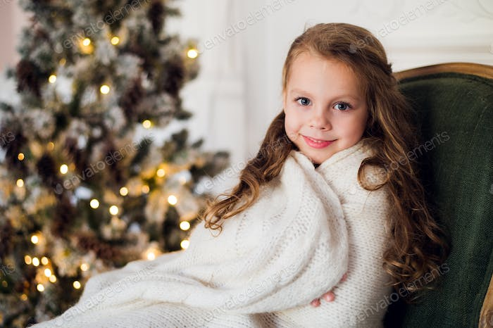 Cute little girl sits by the christmas tree, wrapped in a warm blanket at home