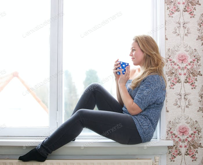 Sitting on windowsill with a  cup of tea