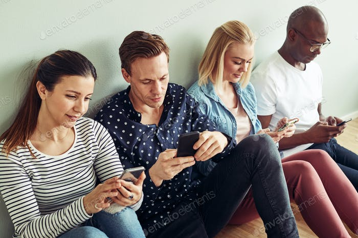 Businesspeople sitting on an office floor using their cellphones