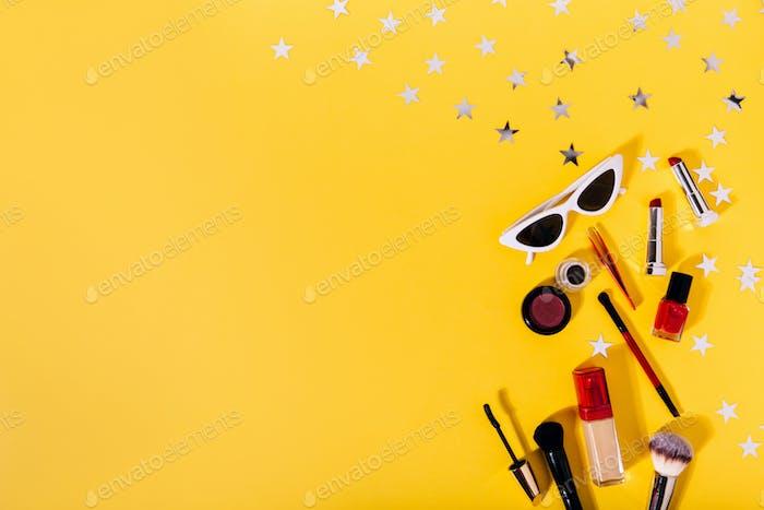 Composition of makeup brushes, tonal foundation, eye liner, lipstick, mascara