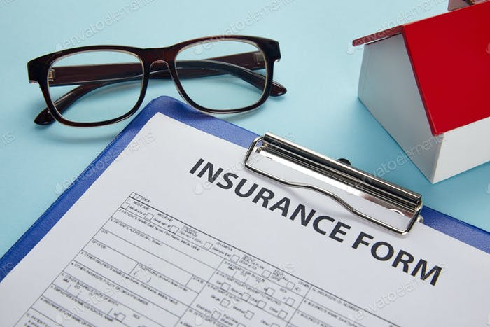 close-up view of insurance form on clipboard, eyeglasses and house model on blue