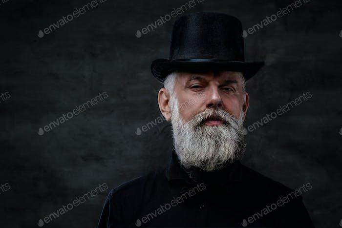altmodischer Großvater in schwarzer Kleidung mit Zylinderhut