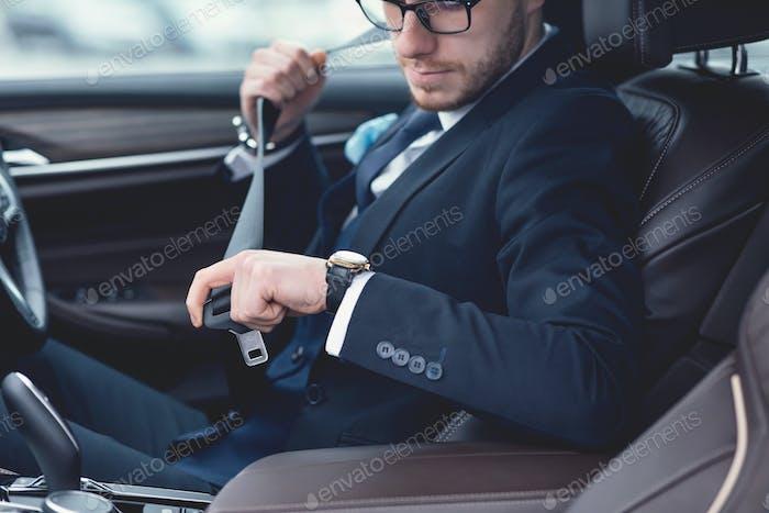 Guy Putting On Seat Belt Sitting In Luxury Car