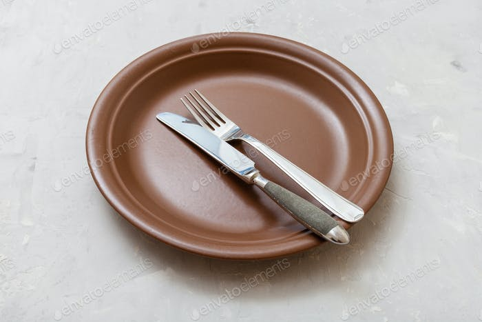 brown plate with parallel knife, spoon on concrete