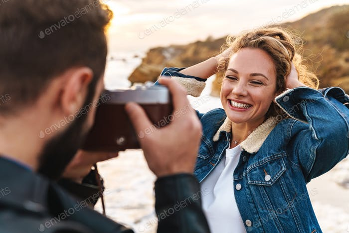 Cheerful pretty young woman posing infront of her boyfriend