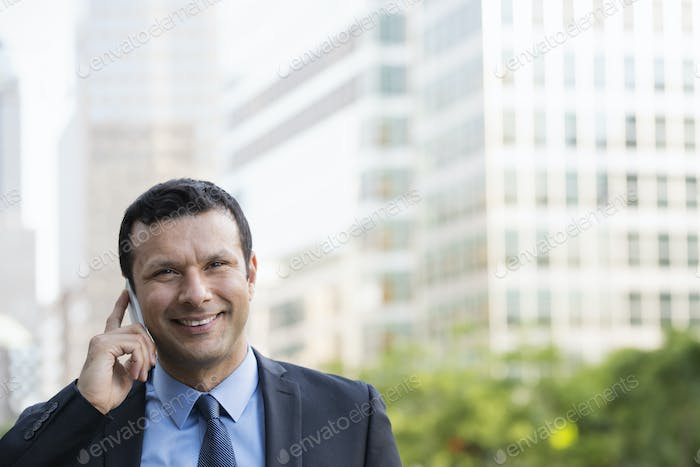 A latino businessman in business suit, using his phone.