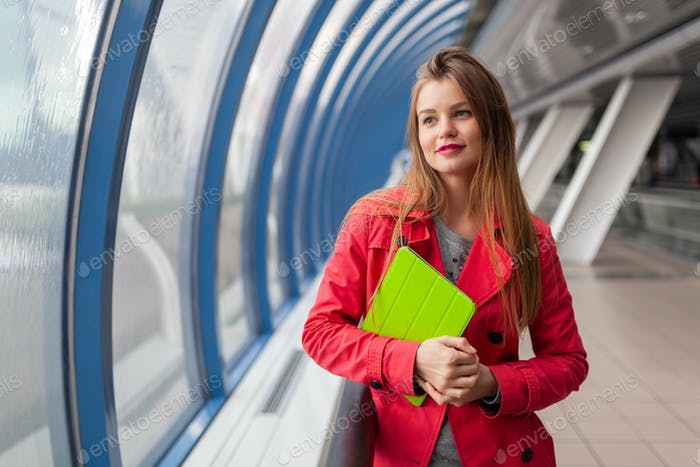 young pretty woman in casual outfit holding tablet laptop in urban building