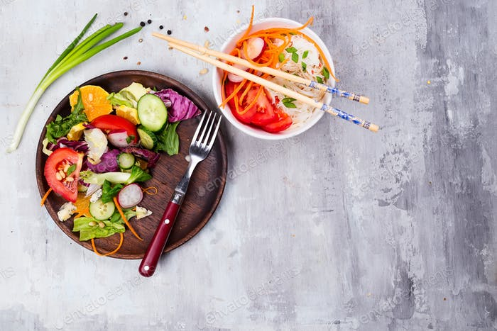 Healthy salad plate with vegetables and with Chinese noodles and carrots on stone background
