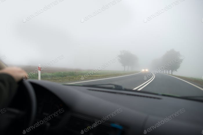 Car driving in thick fog, seen through windscreen of other vehicle