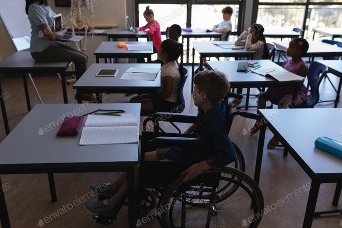 Schoolboy with classmates studying at desk in classroom of elementary school
