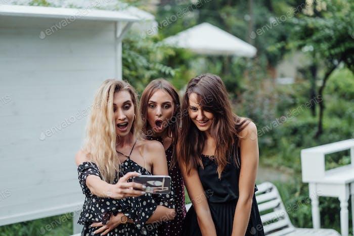Three girls discuss photo