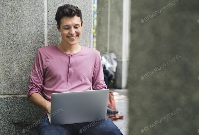 Young Guy Browsing Laptop Campus Concept