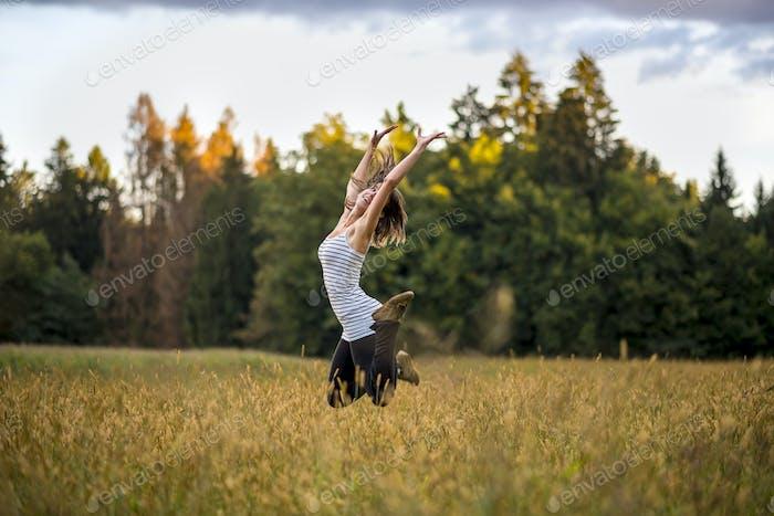 Fröhliche, fröhliche junge Frau springt inmitten einer goldenen Wiese in die Luft