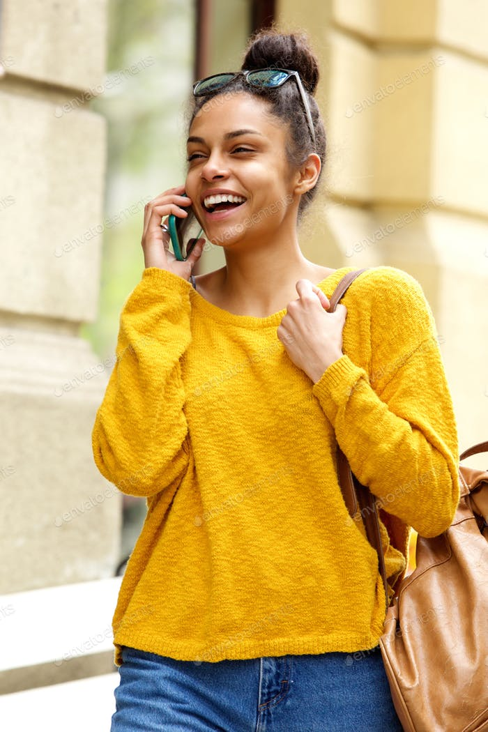 Cheerful woman walking outdoors and talking on mobile phone