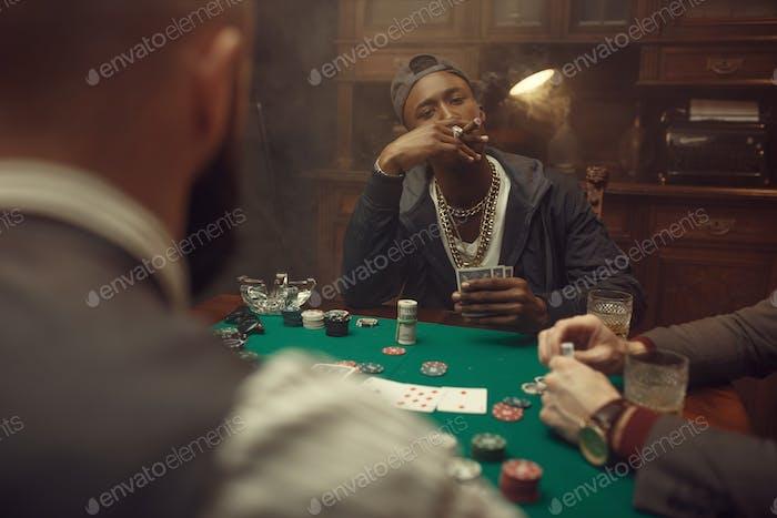 Pokerspieler am Spieltisch mit grünem Tuch