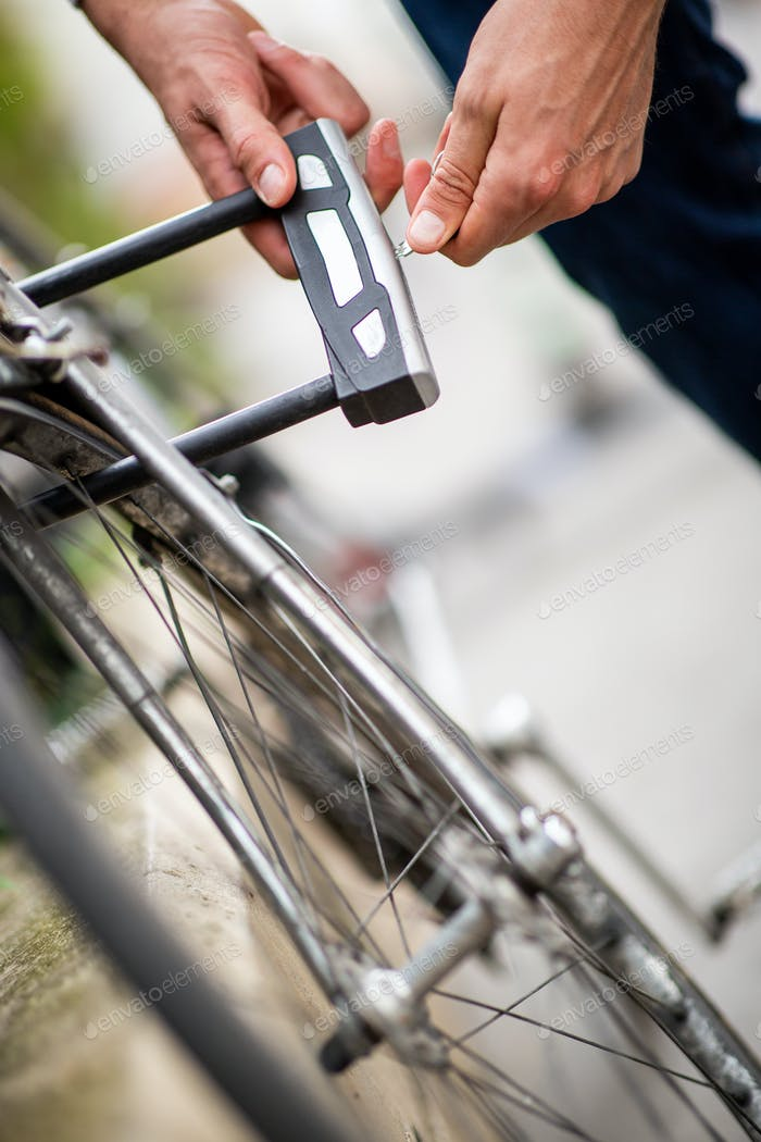 male hands opening lock for bike