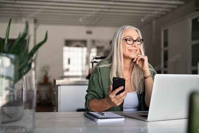 Senior woman using laptop and smartphone