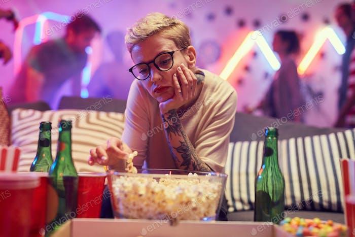 Bored woman eating popcorn