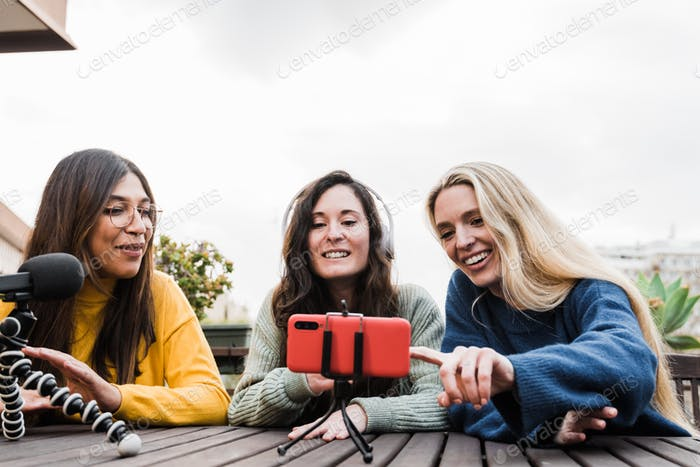 Multiracial friends sharing content on streaming networks with smart phone cam