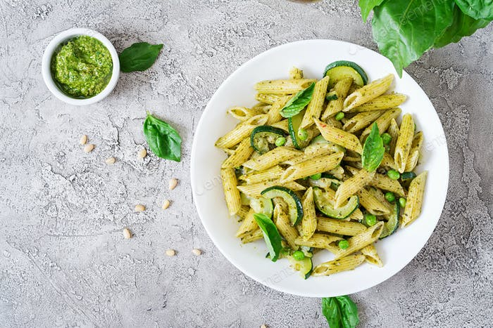 Penne pasta with  pesto sauce, zucchini, green peas and basil. Italian food. Top view. Flat lay.