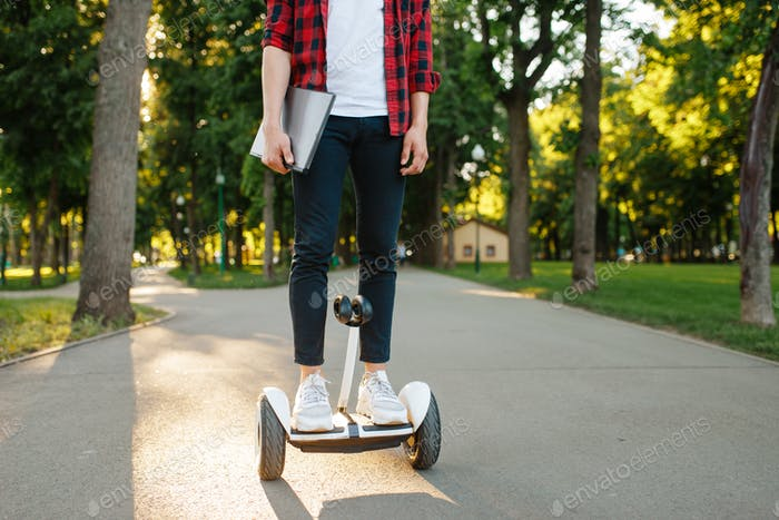 Young man riding on mini gyroboard in summer park