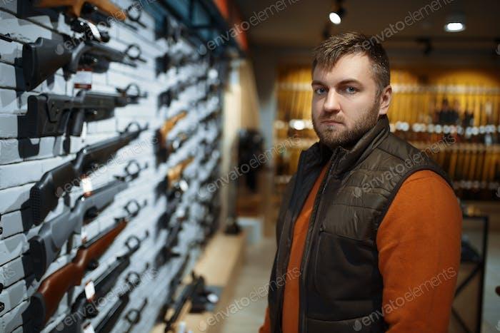 Mann auf Handfeuerwaffen, Schaufenster in Waffen-Shop