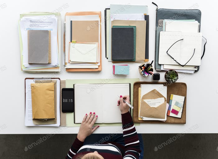 Hands Working on Office Desk with Notebooks and Stationery on Wh