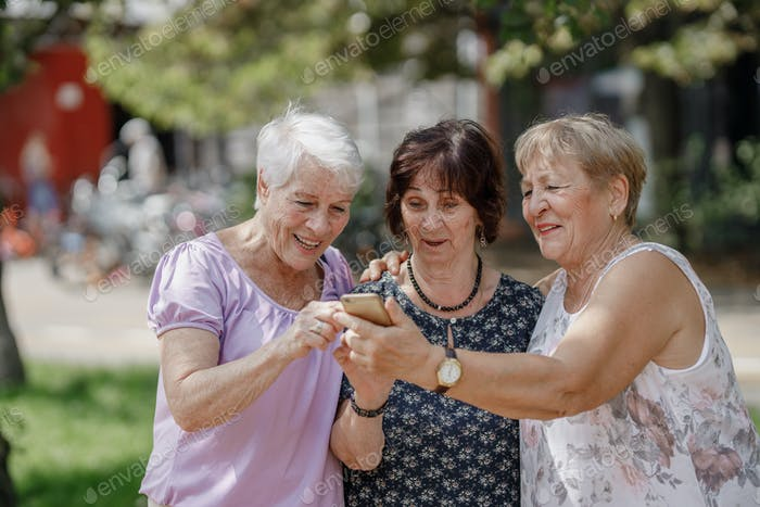 Three old women are smiling and looking photos at the at screen of the phone in the park on a warm