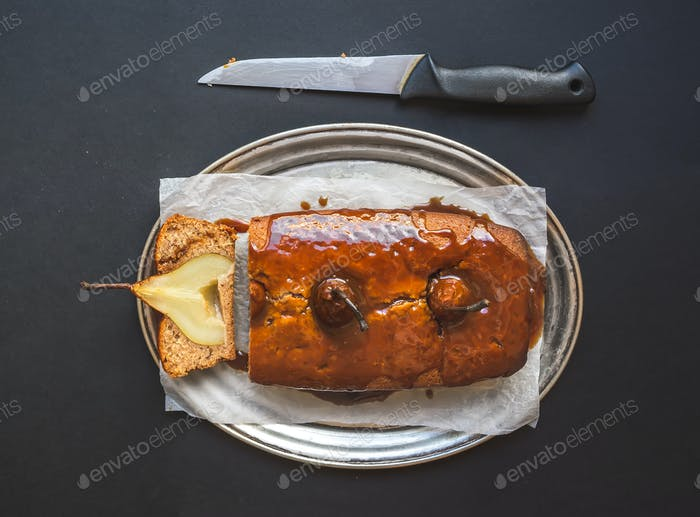 Spicy pear cake with caramel topping on a silver dish on black