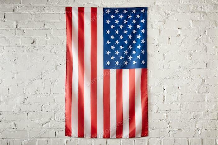 vista de cerca de la bandera de los Estados Unidos de América en la pared de ladrillo blanco